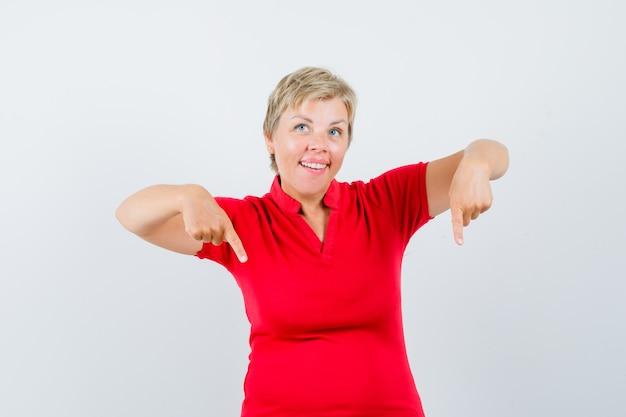 Starsza kobieta w czerwonej koszulce skierowaną w dół i patrząc niepewnie.