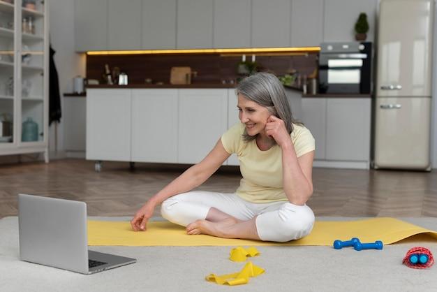Starsza kobieta w domu bierze lekcję fitness na laptopie