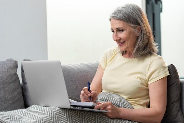 Starsza kobieta w domu na kanapie, korzystająca z laptopa i robiąca notatki