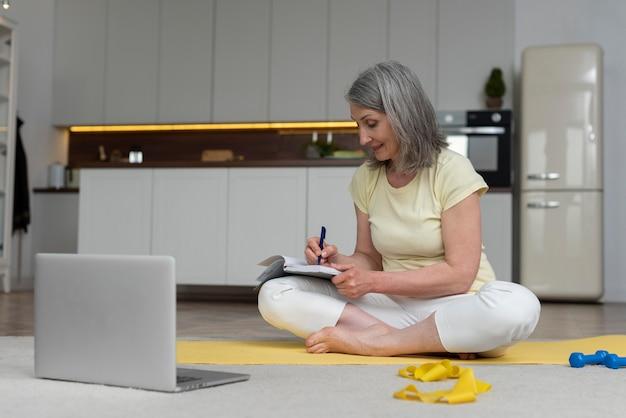 Starsza kobieta w domu studiuje lekcję fitness na laptopie i robi notatki