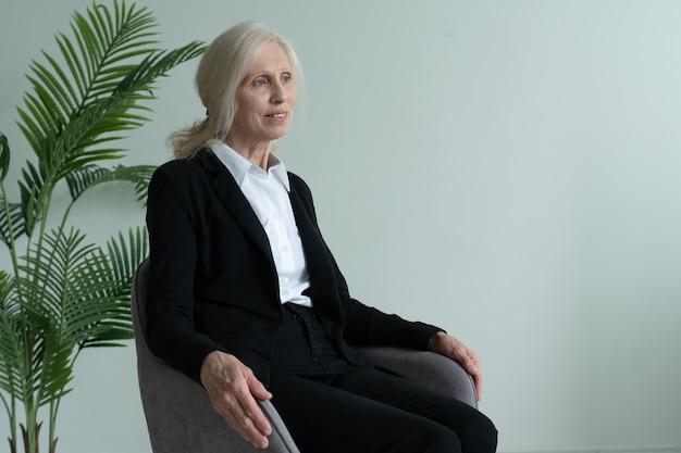 Starsza kobieta w garniturze siedzi na krześle i wygląda przez okno