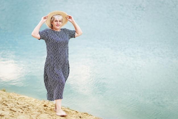 Starsza Kobieta W Kapeluszu Chodzi Boso Po Piasku Nad Wodą Premium Zdjęcia