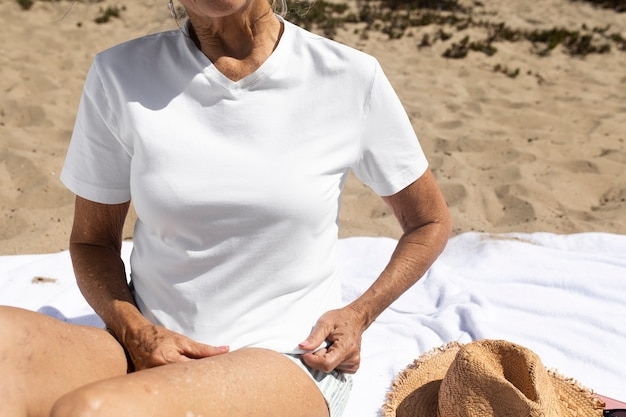 Starsza kobieta w kapeluszu przeciwsłonecznym chłodzi na plaży