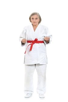 Starsza kobieta w karate pozie na białym tle