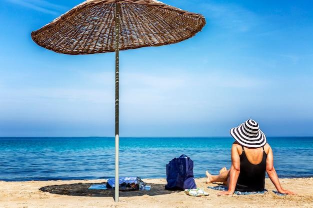 Starsza kobieta w kostiumie kąpielowym i kapeluszu siedzi na piaszczystej plaży nad morzem.