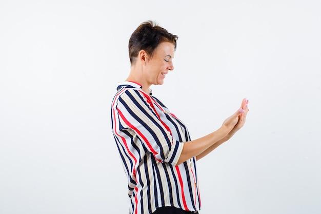 Starsza kobieta w koszuli w paski, patrząc na ręce, jak coś trzyma i patrząc skoncentrowany, widok z przodu.