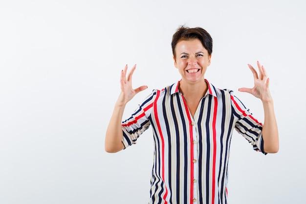 Starsza kobieta w koszuli w paski, podnosząc ręce, ściskając coś i patrząc podekscytowany, widok z przodu.