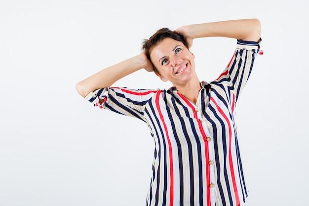 Starsza kobieta w koszuli w paski, trzymając się za ręce na głowie, odwracając wzrok i patrząc szczęśliwy, widok z przodu.