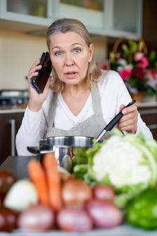 Starsza kobieta w kuchni przygotowuje jedzenie i trzyma inteligentny telefon