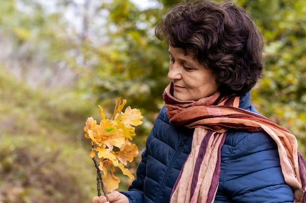 Starsza kobieta w lesie podziwia jesienne liście, kobieta trzyma gałązkę dębu z żółtymi liśćmi