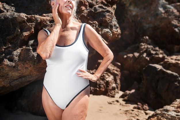 Starsza kobieta w letniej sesji w białym jednoczęściowym stroju kąpielowym