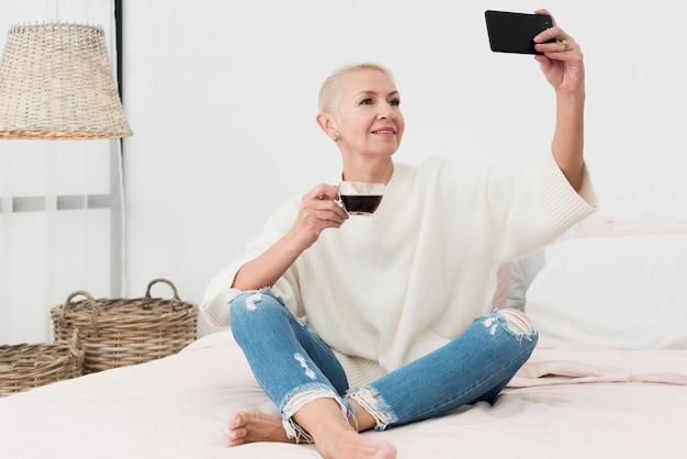 Starsza kobieta w łóżku trzymając kubek kawy i biorąc selfie