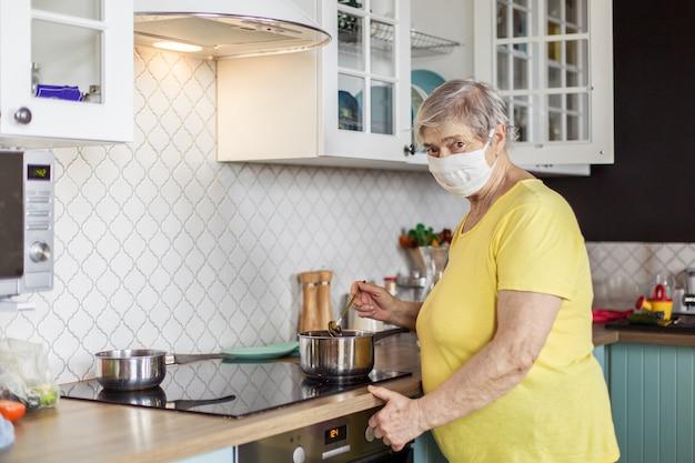 Starsza kobieta w masce kwarantanna europa gotuje w kuchni w mieszkaniu. osoby w podeszłym wieku narażone na koronawirusa covid-19. zostań w domu. babka ochrony przed pandemią zapalenia płuc. niebezpieczeństwo zarażenia