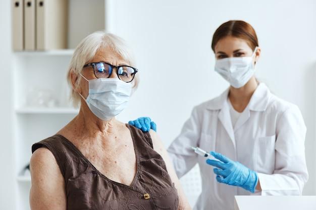 Starsza kobieta w masce medycznej obok ochrony immunologicznej lekarza
