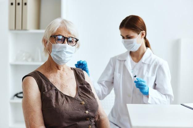 Starsza kobieta w masce medycznej obok paszportu lekarza covid