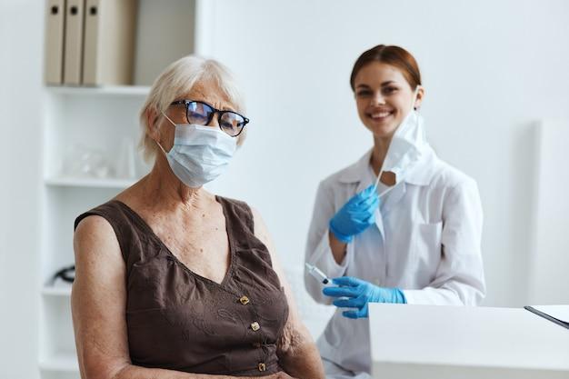 Starsza kobieta w masce medycznej obok paszportu ze szczepionką lekarza