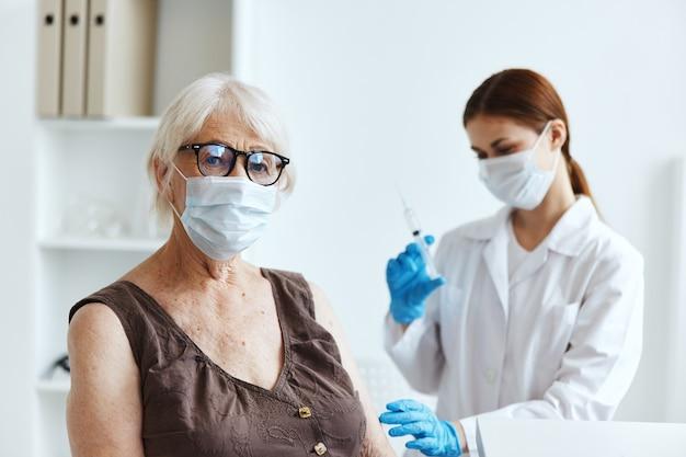 Starsza kobieta w masce medycznej siedząca obok paszportu ze szczepionką pielęgniarki