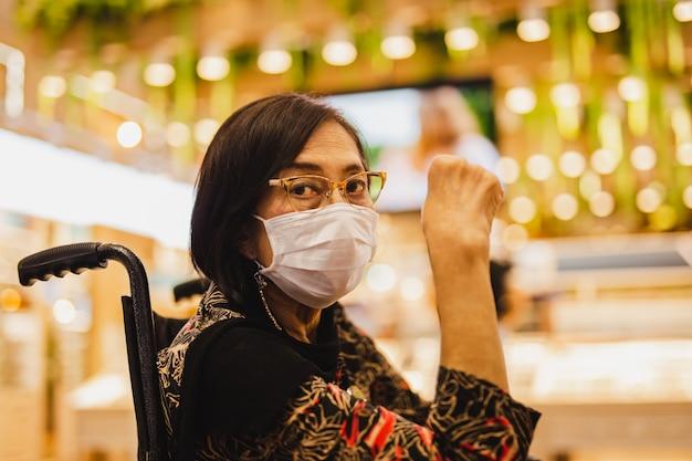Starsza kobieta w masce medycznej siedzi na wózku inwalidzkim w okularach.
