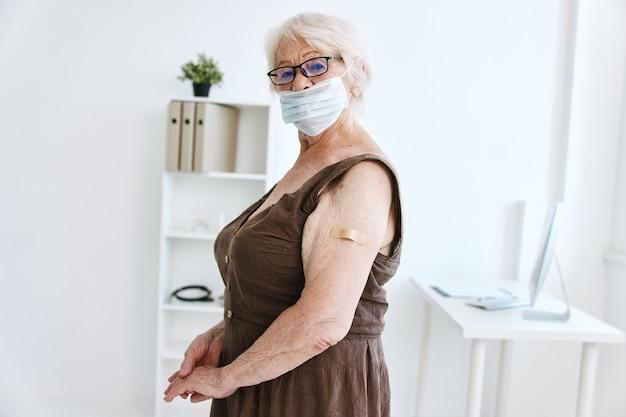 Starsza kobieta w masce medycznej siedzi w paszporcie szczepionki szpitalnej