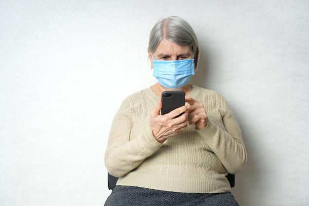 Starsza kobieta w masce medycznej, trzymając smartfon w dłoniach