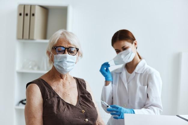 Starsza kobieta w masce medycznej w szpitalu na szczepienia