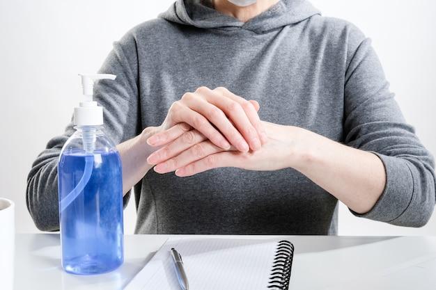 Starsza kobieta w masce ochronnej przeciera ręce żelem antybakteryjnym w miejscu pracy