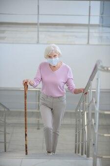 Starsza kobieta w maseczce na twarz wchodzącej na górę