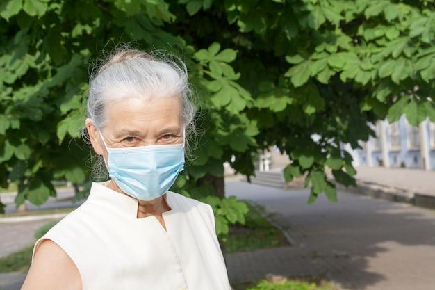 Starsza kobieta w medycznej masce outdoors.