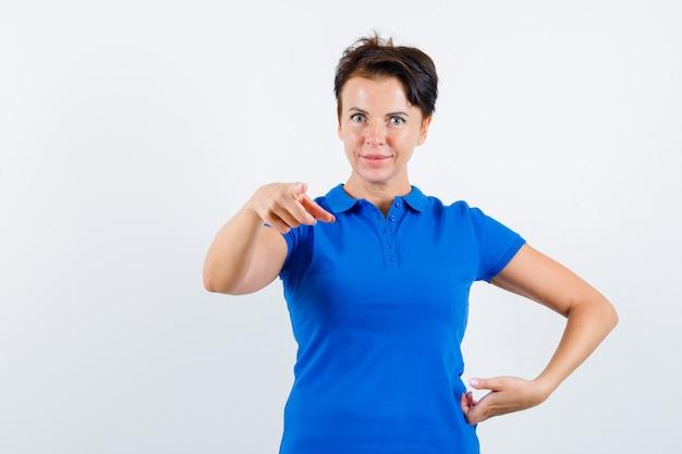 Starsza kobieta w niebieskiej koszulce, wskazując na aparat i patrząc pewnie, widok z przodu.