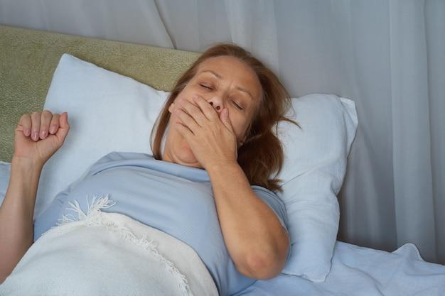 Starsza kobieta w niebieskiej piżamie ziewa leżąc w łóżku, zakrywając usta dłonią