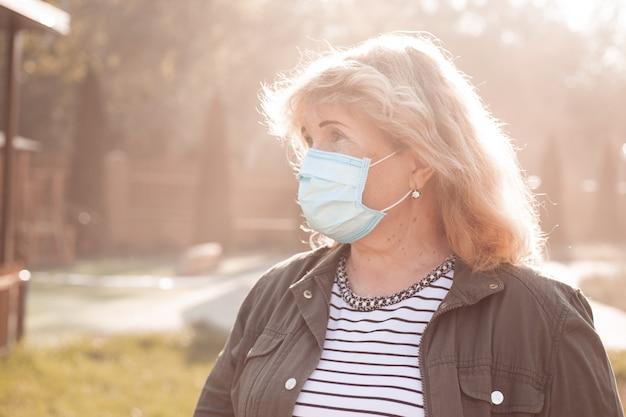 Starsza kobieta w ochronnej masce oddechowej, wybuch choroby wirusowej koronawirusa covid-2019