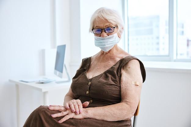 Starsza kobieta w okularach maseczka medyczna paszport szczepionki szpitalnej