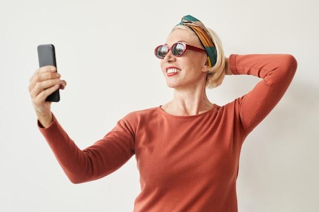 Starsza kobieta w okularach przeciwsłonecznych co selfie na jej telefon komórkowy na białym tle