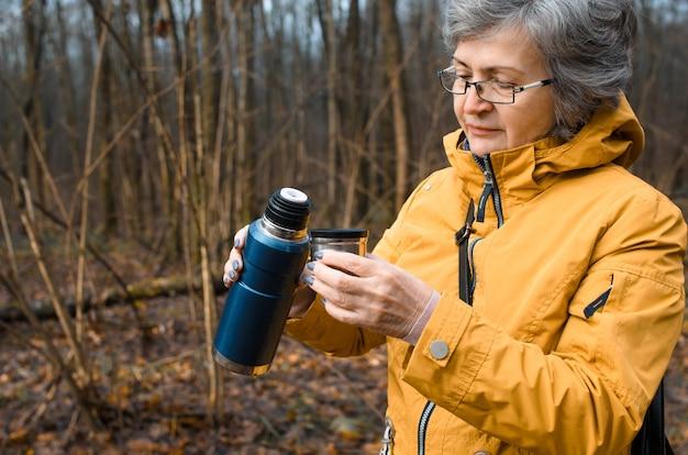 Starsza kobieta w okularach spaceru po lesie. starsza kobieta trzyma kemping termos z gorącym napojem. koncepcja napoju rozgrzewającego w chłodne dni, aktywny tryb życia na emeryturze.