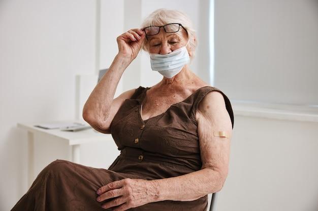 Starsza kobieta w okularach z bandażem na ramieniu paszport szczepionkowy szpital