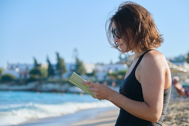 Starsza kobieta w okulary i strój kąpielowy relaksująca czytanie książki i ciesząc się morskim zachodem słońca
