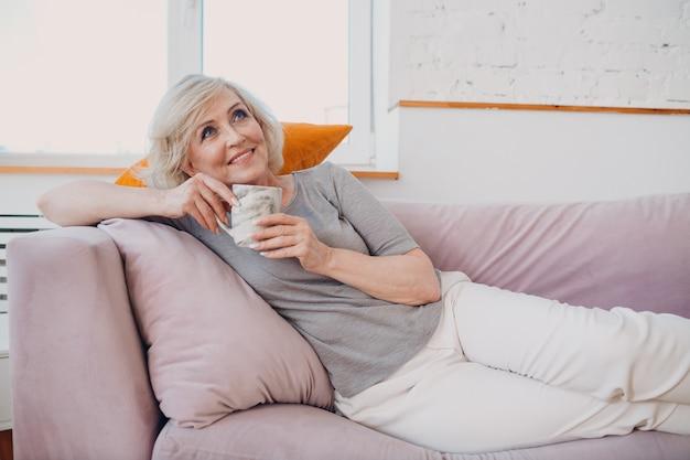 Starsza kobieta w podeszłym wieku, kaukaski, cieszący się napojem popołudniowej herbaty leżącej na kanapie w domu