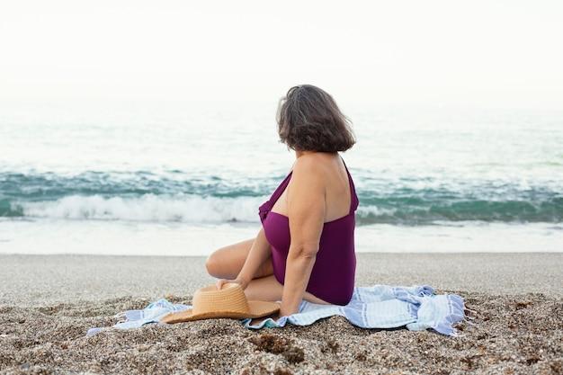 Starsza kobieta w słomkowym kapeluszu ciesząca się swoim dniem na plaży