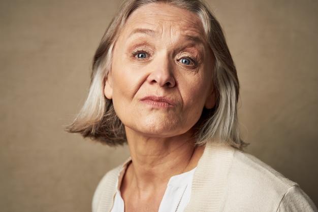 Starsza kobieta w szacie zbliżenie twarzy pozowanie na białym tle
