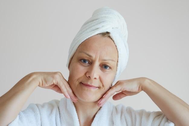 Starsza kobieta w szlafroku z białym ręcznikiem na głowie wykonuje odmładzający masaż twarzy