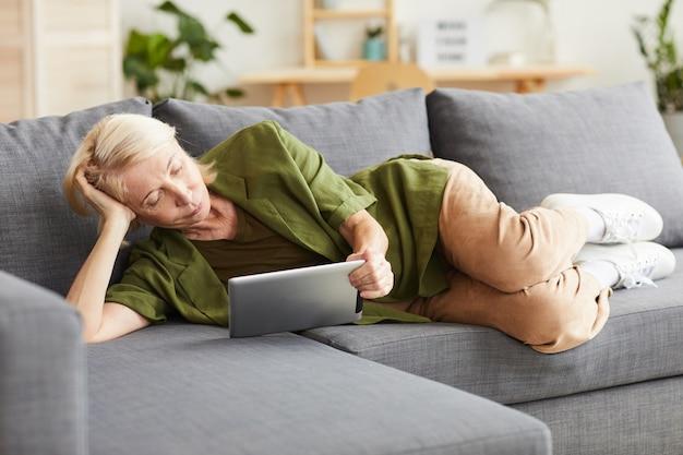 Starsza kobieta w ubranie, leżąc na kanapie i oglądając coś na cyfrowym tablecie w salonie