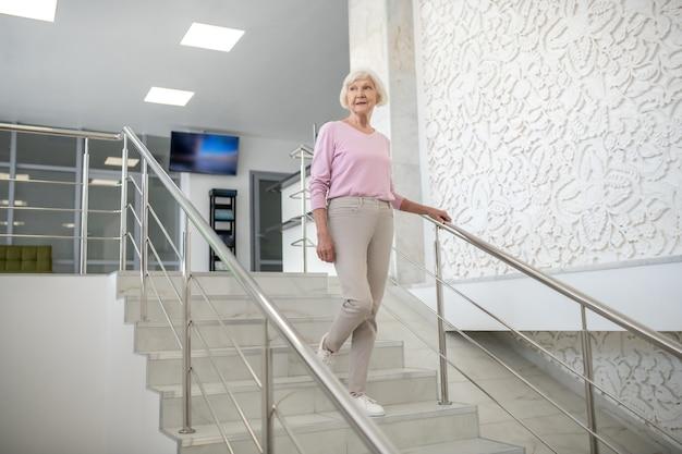 Starsza kobieta w ubranie schodząc na dół
