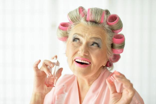 Starsza kobieta w wałkach do włosów w domu