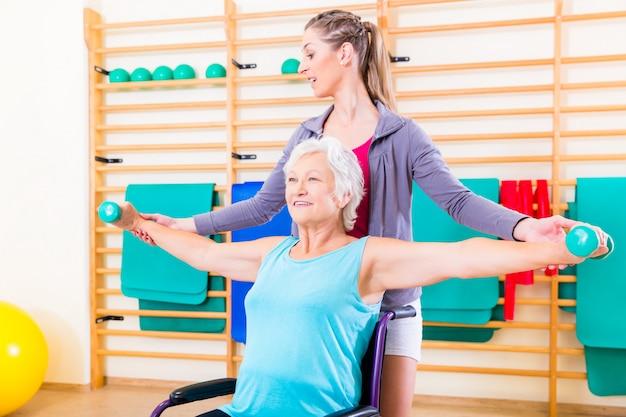 Starsza kobieta w wózku inwalidzkim robi fizycznej terapii