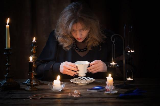 Starsza kobieta wróżka na podstawie kawy