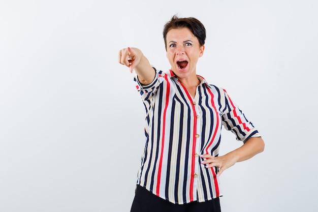 Starsza kobieta, wskazując na coś w pasiastej koszuli i patrząc podekscytowany, widok z przodu.