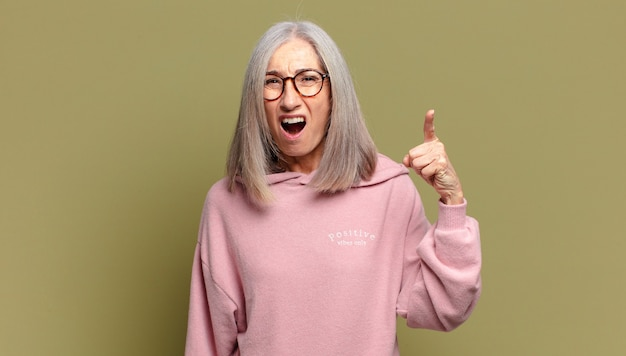 Starsza kobieta wskazująca na kamerę z wściekłym, agresywnym wyrazem twarzy wyglądającym jak wściekły, szalony szef