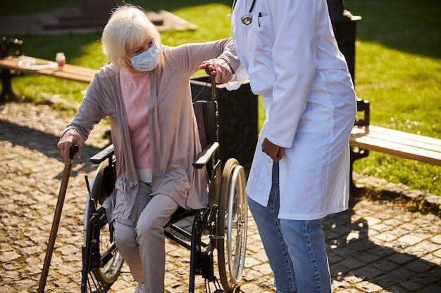 Starsza kobieta wstaje, opierając się na lasce i trzymając za rękę lekarza