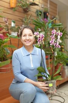 Starsza kobieta wybiera orchidei