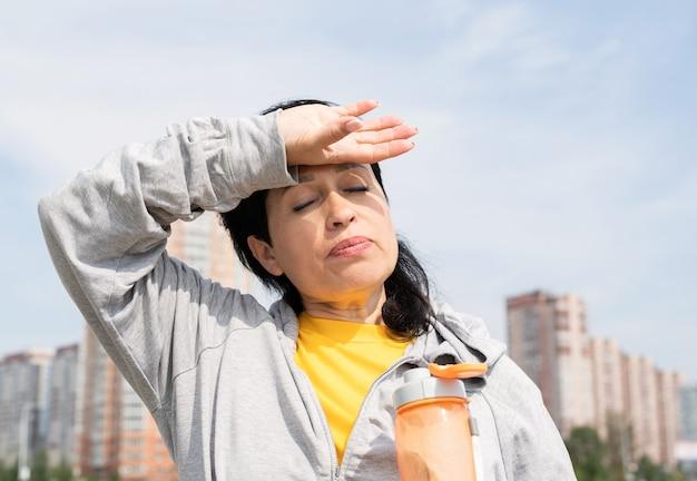 Starsza kobieta wyciera pot po ciężkim treningu na świeżym powietrzu w parku